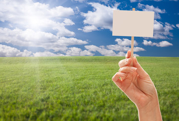 Blank Sign in Hand Over Grass Field and Sky