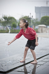 happy asian girl play by Fountain