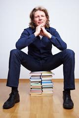 Mann sitzt auf Büchern