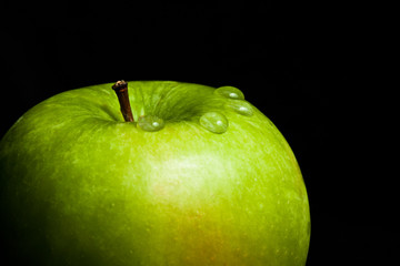 A wet green apple on black background (close-up)