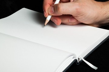 Male hand writing with a pencil in a blank book (close-up)