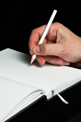 A male hand writing with a pencil in a blank book