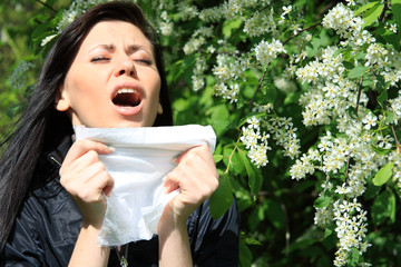 allergy to pollen: young woman sneezing among flowers