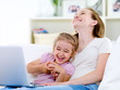 Laughing mother and daughter with laptop