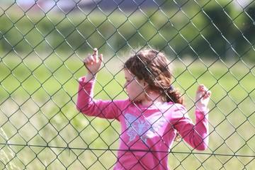 Mädchen hinter Zaun
