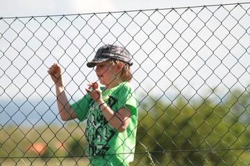 Junge überwindet Zaun