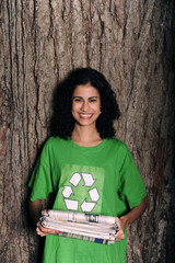 woman with recycling sign on shirt holding newspapers