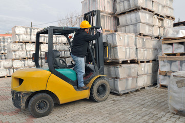 Forklift operator working at warehouse.