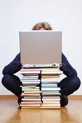 Mann mit Laptop und Büchern