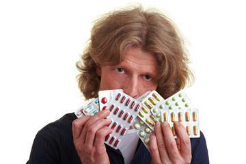 Mann hält Tabletten vor Gesicht