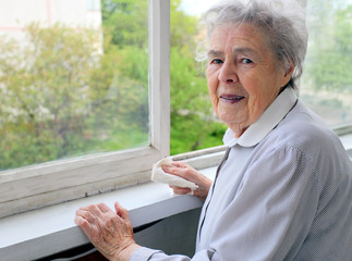 Portrait of senior woman standing at the window