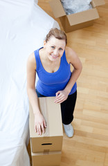 Positive woman is moving various boxes