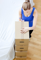 Caucasian woman is moving various boxes