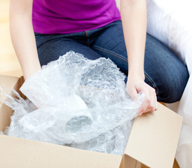 Young woman unpacking box