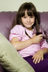The girl with a juice glass on a sofa