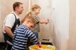 Vater malert Wand mit Söhnen