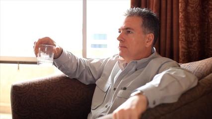 Man Sitting by a Window Having a Drink