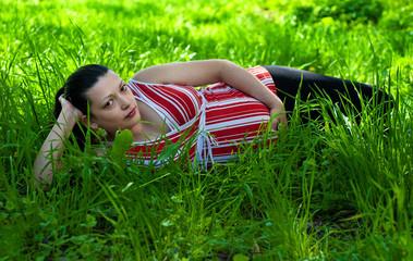 pregnant woman lies on green grass