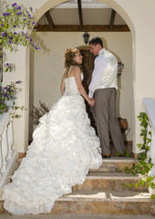 Bride and Groom holding hands on steps of house