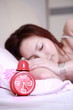 young asian sex girl sleeping on bed with clock