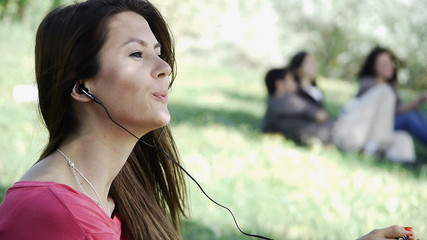 Girl sitting listening outdoor grass