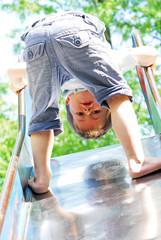 Junge klettert die Rutsche rauf