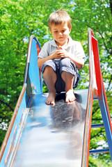 Junge sitzt oben auf der Rutsche