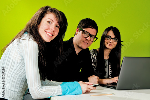 Two attractive girls and a guy working in office
