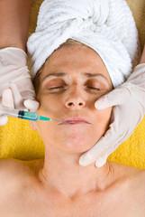 Botox shot in senior woman lips