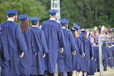 Line of school graduates in blue caps and gowns