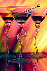 Three martinis in glasses with curved stems