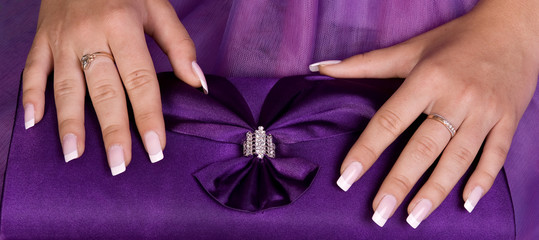 Beautiful hands with french manicure holding purple purse