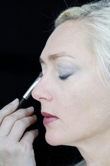 Woman gets make up applied to her face