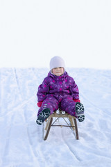Cute little girl sledging in the snow during winter