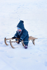 Adorable little gir sitting on a wooden sledge