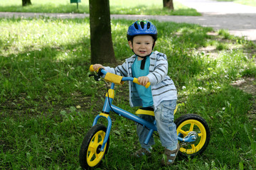 Child learning to ride on his first bike without pedals