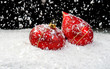 Snow falling on two red ornaments