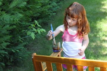 Petite fille met de l'huile de teck