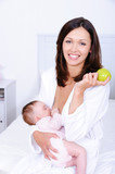 Woman with green apple breastfeeding her baby poster