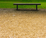 Empty Bench Between Sawdust and Grass