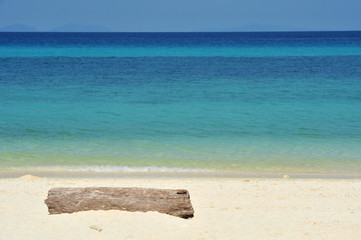 Timber on a white sandy beach.