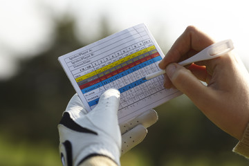 Writing golf handicap with a glove.