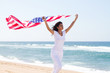 woman holding USA flag on beach