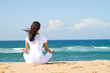 back view of woman meditating on beach