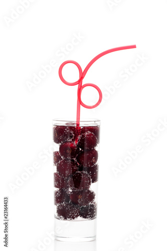 Cherries with a straw in glass isolated on a white background