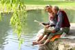 Großvater und Enkelin beim Zeitunglesen im Grünen am Teich