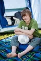 junge mit fußball vor dem zelt