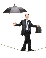 A businessman with an umbrella and a briefcase on a tightrope