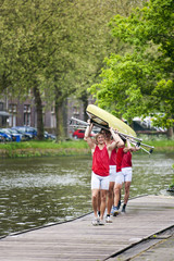 Oarsmen carrying a rowing boat