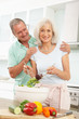 Senior Couple Preparing Salad In Modern Kitchen